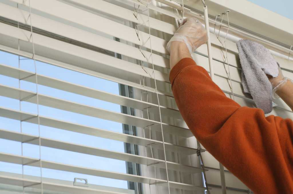 Woman cleaning blinds with duster